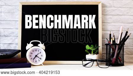The Word Benchmark Is Written On The Chalkboard Next To The White Alarm Clock, Glasses, Potted Plant