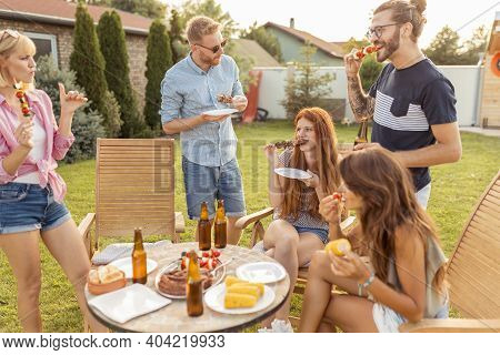 Group Of Cheerful Young Friends Gathered Around The Table, Eating Grilled Meat, Drinking Beer And Ha