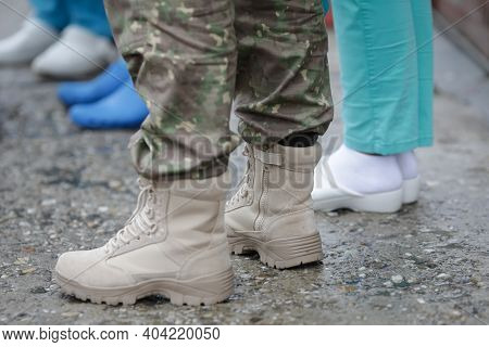 Shallow Depth Of Field (selective Focus) Image With The Boots Of A Female Soldier And A Medic.