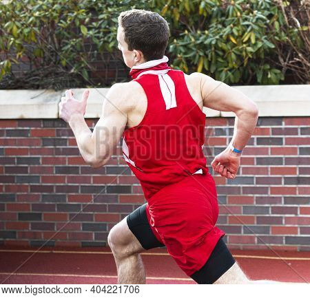 A Male High School Track Runner Is Sprinting A Race On An Outdoor Track Next To A Brick Wall With Pa