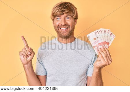 Young blond man holding colombian pesos smiling happy pointing with hand and finger to the side