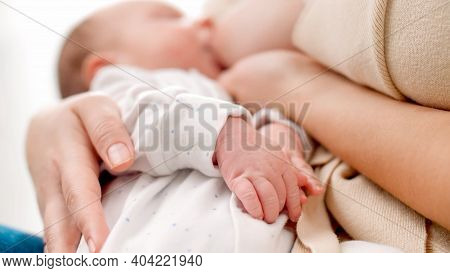 Closeup Of Newborn Babys Hands Lying On Mother While Sucking Breast And Eating Milk. Concept Of Heal