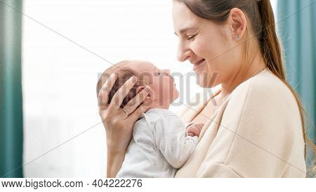 Portrait Of 2 Weeks Old Little Baby Boy With Young Caring Mother Against Big Window At House. Concep
