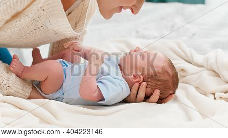 Young Caring Mother Putting Her Little Baby Son On Soft Blanket In Bedroom. Concept Of Family Happin