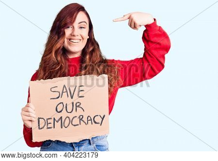 Young beautiful woman holding save our democracy protest banner pointing finger to one self smiling happy and proud