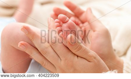 Closeup Shot Of Young Mother Gently Holding And Touching Little Feet Of Her Newborn Baby Boy Lying I