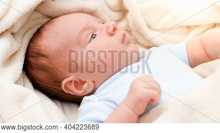 Above View On Adorable Newborn Baby Covered In Soft Blanket Lying In Crib.