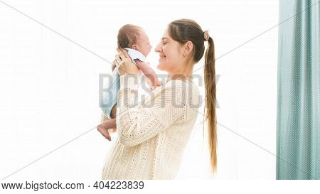 Happy Smiling Woman With Little 1 Months Old Baby Boy Hugging And Embracing At Big Windw In Bedroom.