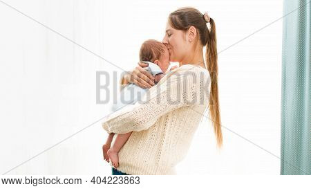 Happy Smiling Young Mother Cuddling And Kissing Her Newborn Baby Boy Against Bright Sun Shining Thro