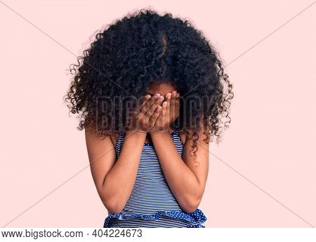 African american child with curly hair wearing swimwear with sad expression covering face with hands while crying. depression concept.