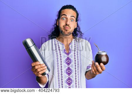 Young handsome man with long hair drinking mate infusion puffing cheeks with funny face. mouth inflated with air, catching air.