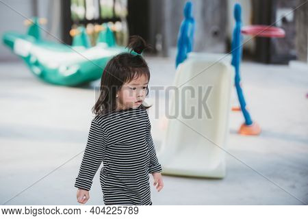 Little Girl In A Moody Mood. Children Peck Their Fingernails. Background Is A Playground, Simulating