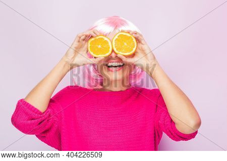 Caucasian Woman With Pink Wig And Sweater, With Two Orange Slices In His Eyes Posing Funny At The Ph