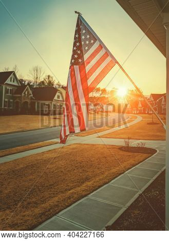 American flag outside residential home at dawn