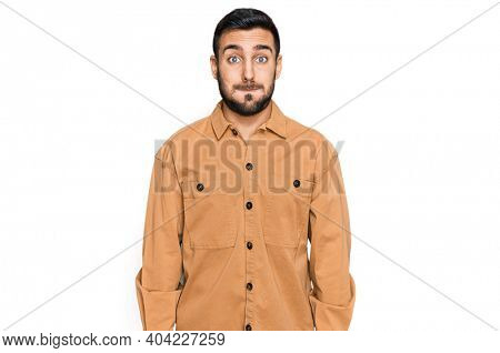 Young hispanic man wearing casual clothes puffing cheeks with funny face. mouth inflated with air, crazy expression.