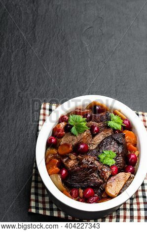 Braised  Beef With Cranberries In Clay Bowl On Black Stone Background