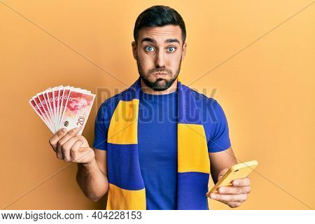 Young hispanic man football supporter using smartphone holding israel shekels banknotes puffing cheeks with funny face. mouth inflated with air, catching air.