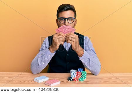 Handsome hispanic croupier man sitting on the table with poker chips and cards relaxed with serious expression on face. simple and natural looking at the camera.