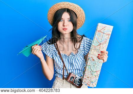 Young beautiful caucasian girl holding paper plane and city map puffing cheeks with funny face. mouth inflated with air, catching air.