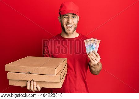 Young caucasian man holding delivery box and swiss franc banknotes winking looking at the camera with sexy expression, cheerful and happy face.