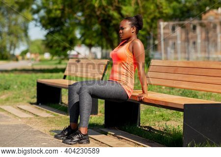 fitness, sport and healthy lifestyle concept - young african american woman doing bench triceps dip outdoors