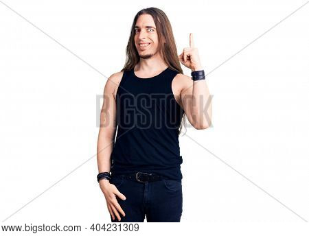 Young adult man with long hair wearing rocker style with black clothes and contact lenses pointing finger up with successful idea. exited and happy. number one.