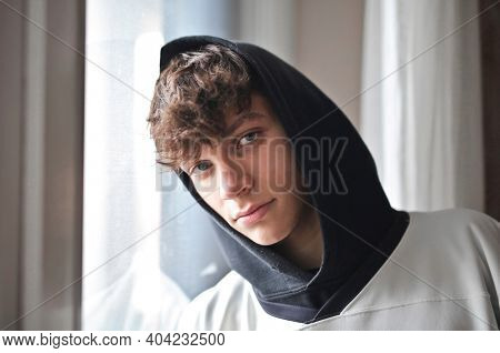 portrait of a young boy leaning against a window