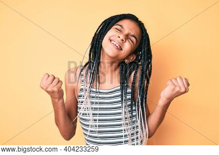 Young african american girl child with braids over yellow background very happy and excited doing winner gesture with arms raised, smiling and screaming for success. celebration concept.