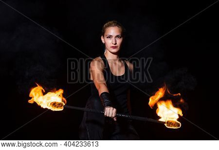 Sexy Woman Performer Twirl Burning Baton During Fire Performance In Dark Night Outdoors, Partyin