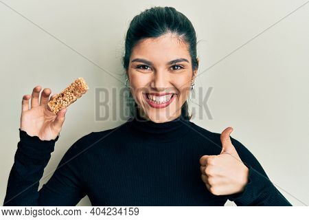 Young hispanic woman eating protein bar as healthy energy snack smiling happy and positive, thumb up doing excellent and approval sign