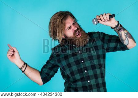 Male Singer With Microphone. Karaoke Concept. Bearded Man In Checkered Shirt Sing A Song. Casual Guy