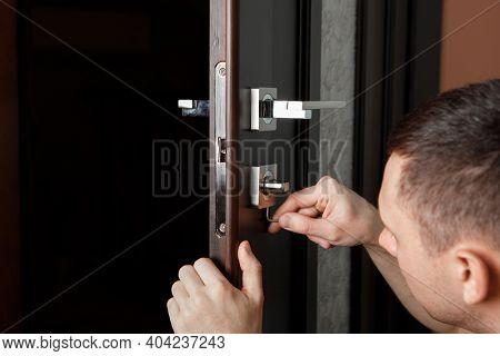 man repairing the doorknob. Carpenter working on lock installation with out the door knobs wood door