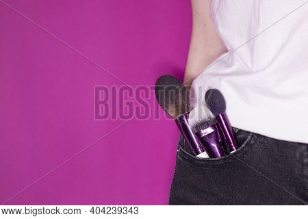 Makeup Brushes Sticking Out Of Black Jeans Pocket On Colorful Pink Background. Professional Makeup A