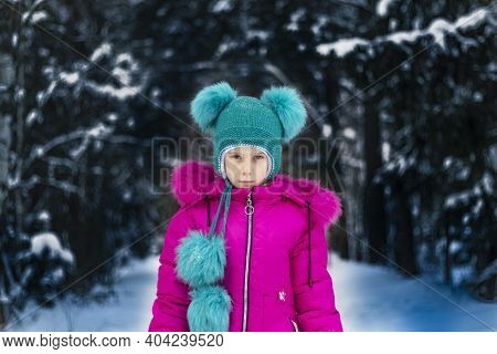 Natural Light. A Girl In A Red Jacket And A Green Hat Is Surrounded By A Lot Of Snow. He Looks At Us