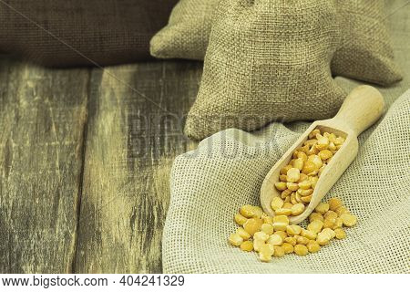 Peas In A Scoop And Bag On A Wooden Background With Space For Text. Burlap Yellow Split Peas With Wo