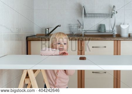 Little Girl In Kitchen Reaches For Candy On The Table. Forbidden Sweets.