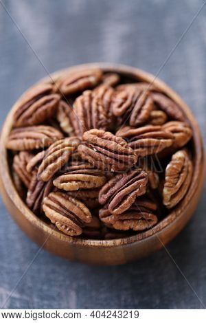 Pecan Nut Close-up In A Round Wooden Cup On A On Wooden Table Background.nuts And Seeds. .healthy Fa