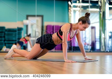 Beautiful Slim Athletic Woman In The Sportswear Doing Fitness Exercises In The Gym. Athlete Enjoys H