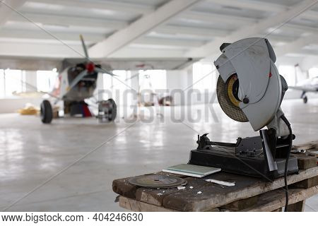 Circular Saw In Aerodrome Hangar In Front Of Small Aircraft