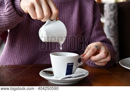 Young Woman Hands Hold White Ceramic Milk Jug With Dripping Drop Into Coffee Cup. Pouring Milk Into