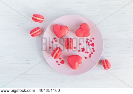 Pink French Heart-shaped Macarons On A Plate. White Wooden Background. Flat Lay. Place For Text.