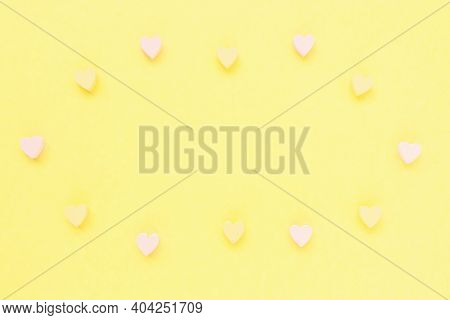 Romantic Abstract Pastel Yellow Backround With Woooden Hearts Decoration. Love, Dating And Valentine