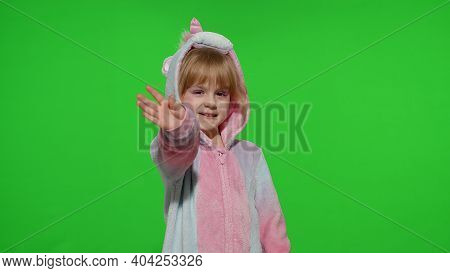 Hello Or Bye. Little Smiling Blonde Child Girl 5-6 Years Old In Unicorn Costume Posing Waving Greeti