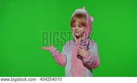 Child Girl In Unicorn Pajamas Costume Using, Holding Smartphone. Kid Pointing At Something With Hand