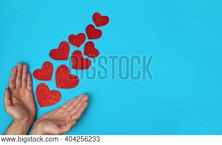 Mans Hands Near Shiny Hearts On On Blue Background. Falling In Love Concept. Flatlay. Top View. Copy