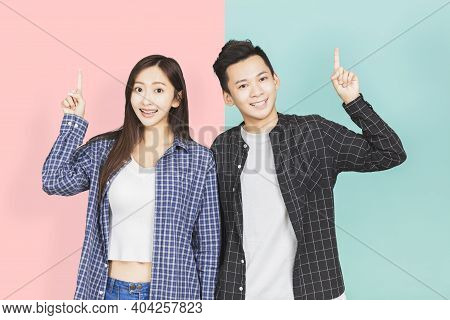 Happy  Young Asian Couple Pointing Up Background