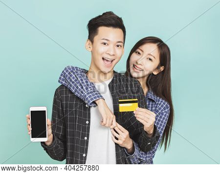 Young Asian Couple Holding Credit Card And Smartphone For Shopping Online Concepts