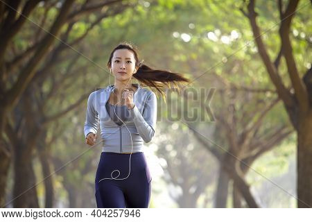 Asian Young Woman Running In The Forest At  Morning