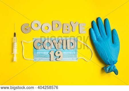 Words Goodbye Covid 19 From Wooden Letters And Syringe With Vaccine, Inflated Medical Glove Waving B