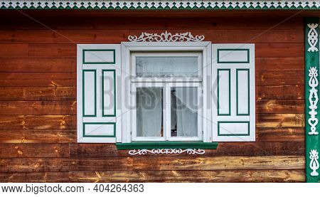 Window with decorative, wooden shutters, Poland
